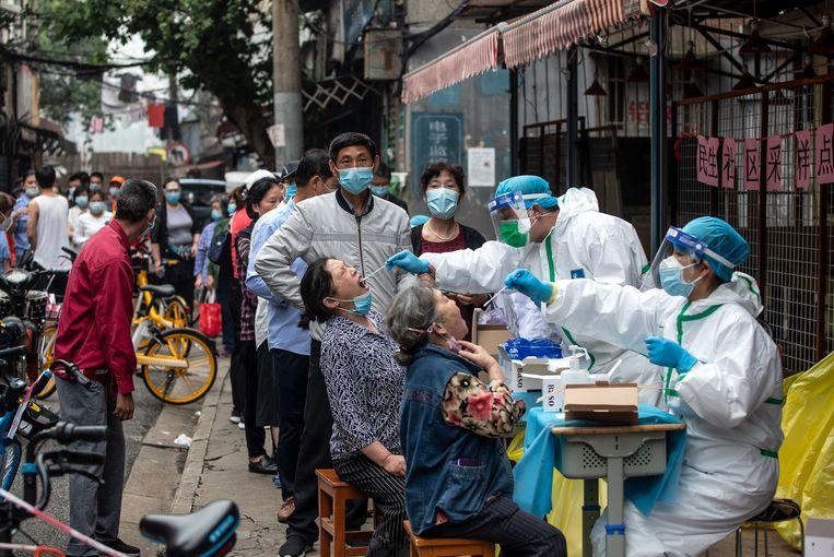 Zorgmedewerkers nemen monsters af in Wuhan, China.  Beeld AFP