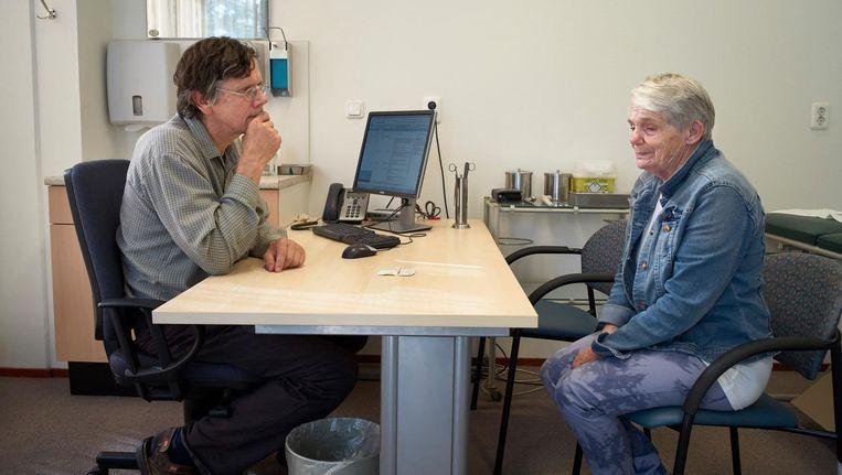 Een huisarts hoort een oudere vrouw aan tijdens het spreekuur in een bejaardenhuis. Beeld anp