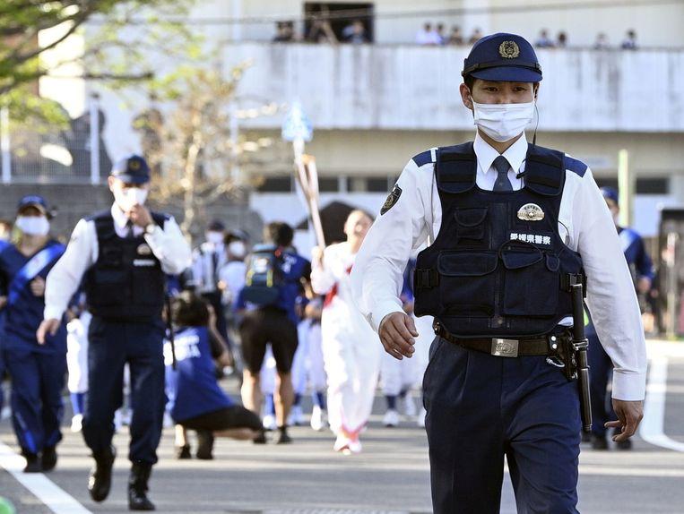 Politieagenten begeleiden de olympische vlam op haar tocht door Japan.  Beeld Reuters