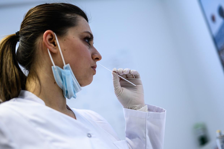 Een vrouw test zichzelf met een sneltest in Moers, Duitsland. Beeld Getty Images