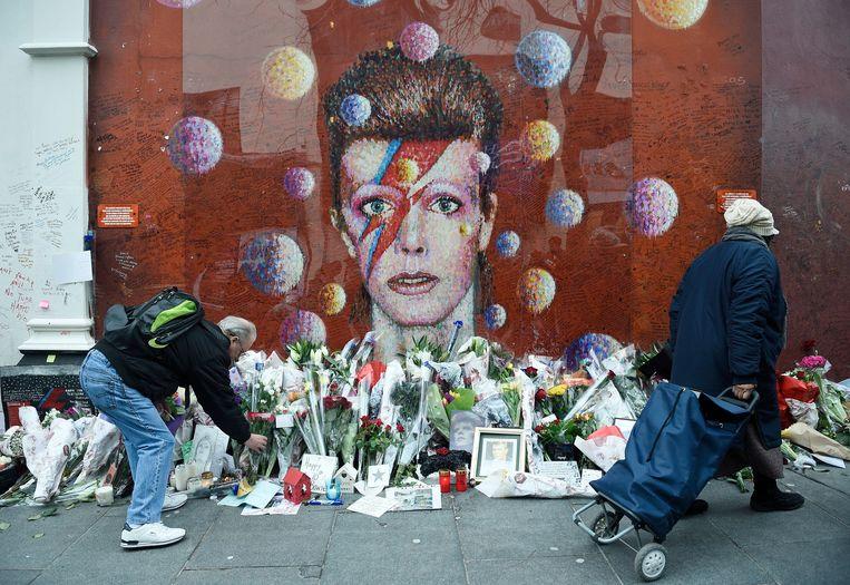 David Bowie fans leggen bloemen neer bij een muurschildering van de artiest die in 2016 overleed. Beeld Hollandse Hoogte / European Press Agency (EPA)