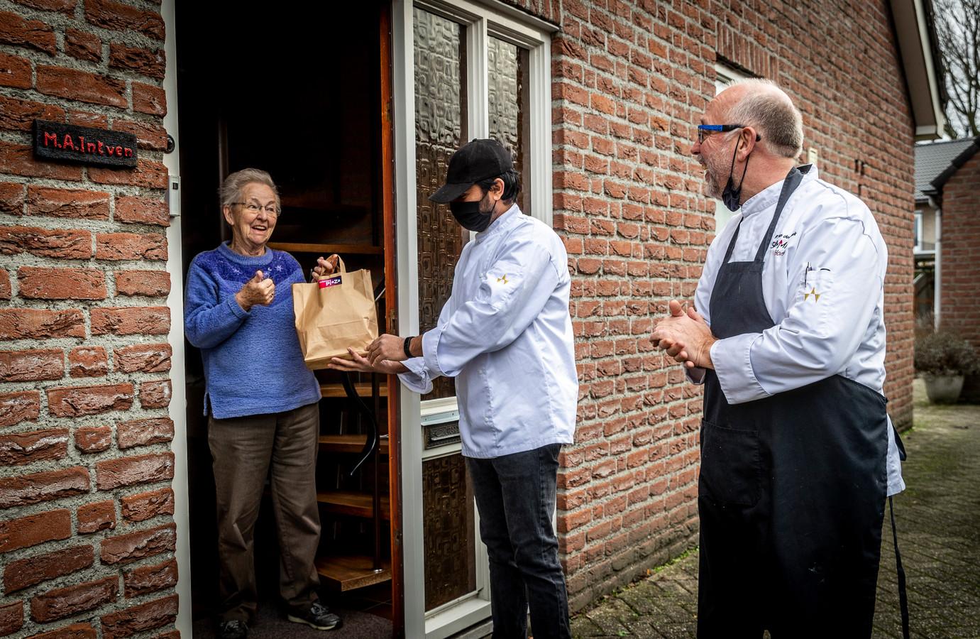 Peter van den Broek (r)  en Abraham leveren 45 lunches voor KBO-leden af in Veldhoven. Mevrouw Toos Intven was een van de gelukkigen.