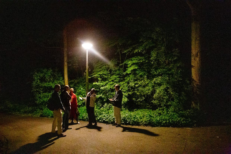 Deelnemers lezen een gedicht onder een lantaarnpaal.  Beeld Pauline Niks