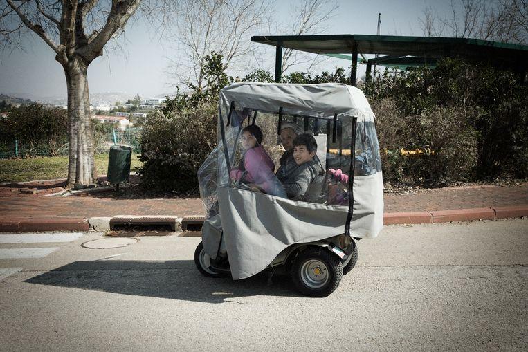 Een oma rijdt met haar kleinkinderen door de nederzetting Eli op de Westelijke Jordaanoever.  Beeld Daniel Rosenthal