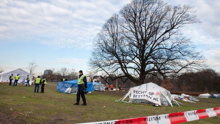 Agenten ruimen de laatste resten van het tentenkamp op, nadat zij het kamp van uitgeprocedeerde asielzoekers hebben ontruimd in Den Haag, eind vorig jaar. Beeld ANP