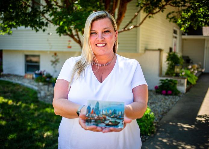 Kim Draper met de kaart, die exact 26 jaar nadat het op de post gedaan werd, bij haar thuis werd bezorgd.