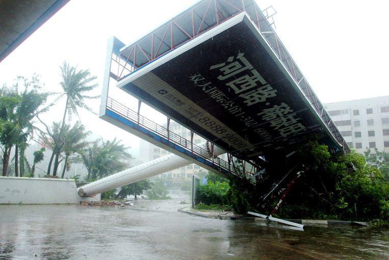 Een omgevallen reclamebord in de Chinese provincie Hainan nadat de tot tropische storm gedegradeerde tyfoon Haiyan zondag en maandag passeerde. Beeld AFP