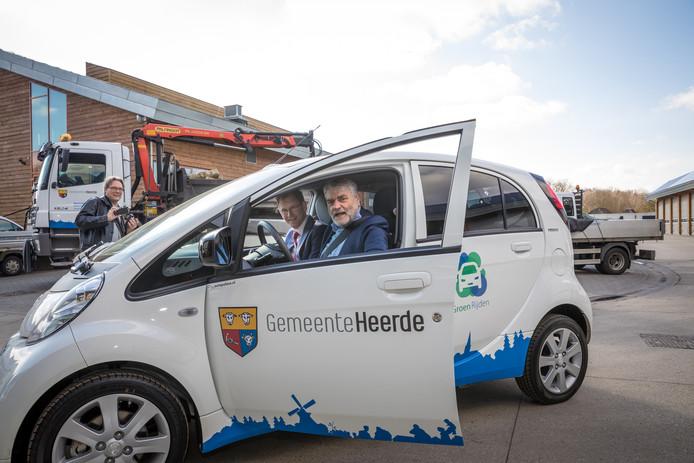 Wethouders Van Dijk (achter het stuur) en Meijer in de eerste elektrische auto van de gemeente Heerde.
