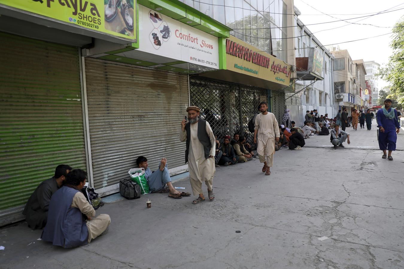 Afghanen in een winkelstraat waar veel uitbaters besloten hebben om hun zaak te sluiten.