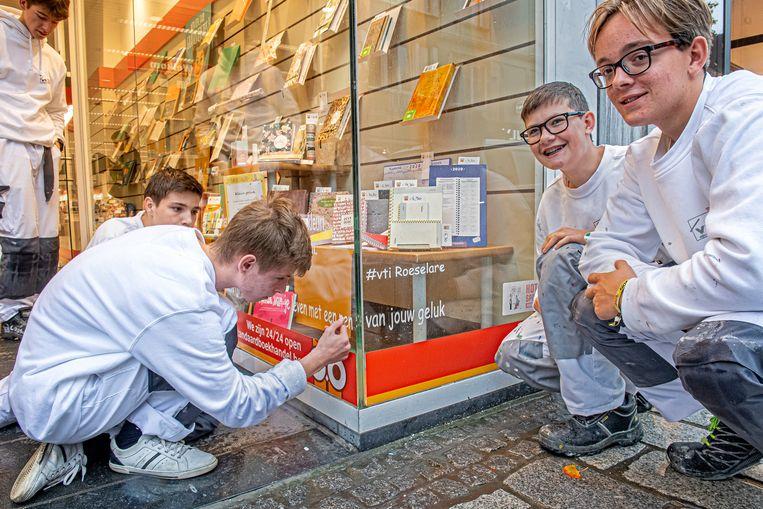 Leerlingen van het VTI brengen spreuken aan op de etalage van de Standaard Boekhandel.