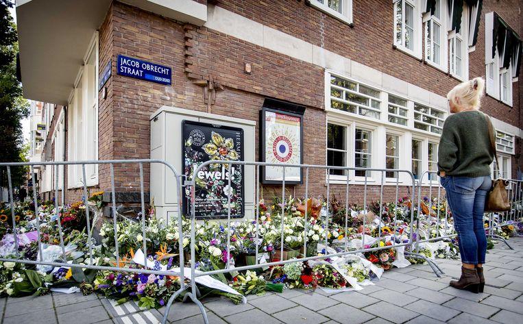 Een passant bij de bloemen die zijn neergelegd voor het kantoor van de doodgeschoten advocaat Derk Wiersum. De raadsman van kroongetuige Nabil B. werd op straat in Amsterdam-Buitenveldert geliquideerd. Beeld ANP