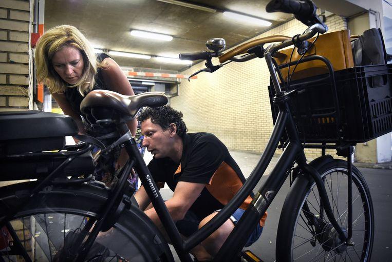 Een mobiele fietsenmaker bij het bedrijf MN (pensioenbeheerder) helpt een werkneemster met haar fiets. Beeld Marcel van den Bergh