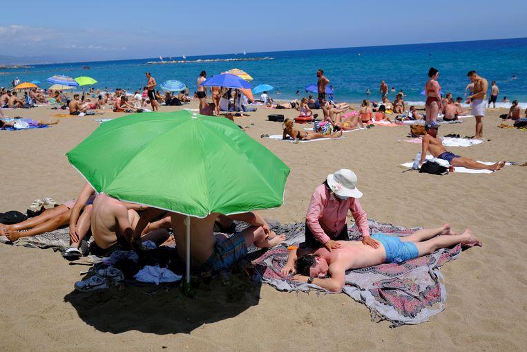 Een toerist op het strand van Barcelona krijgt een massage. Beeld Reuters