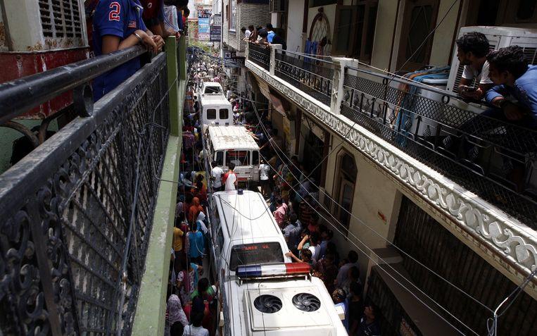 Ambulances wachten om de elf lichamen mee te kunnen nemen uit het huis.
