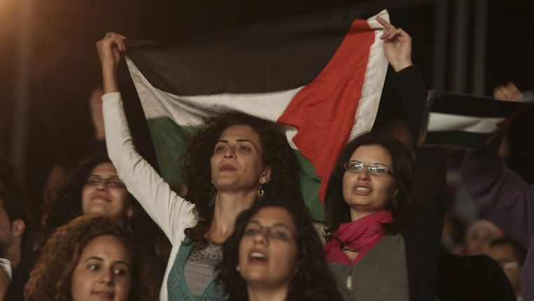 Een Palestijnse vrouw houdt een Palestijnse vlag omhoog bij een optreden van de Egyptische band Wast El Balad. Beeld epa