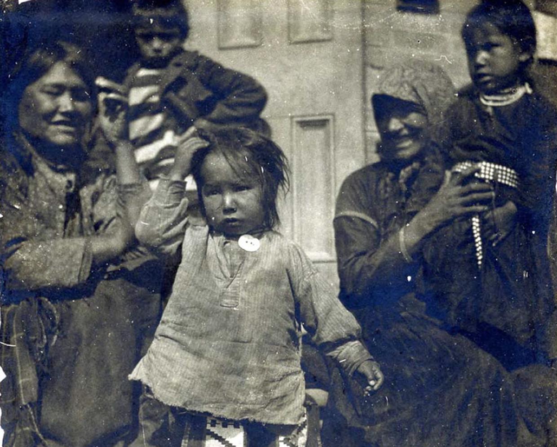 Inheemse kinderen en hun moeders aan de Regina Indian Industrial School, 1905. Hun eigen taal en cultuur moesten ze vergeten. Zo'n 150.000 kinderen werden tussen 1883 en 1996 bij hun ouders weggehaald.     Beeld EPA