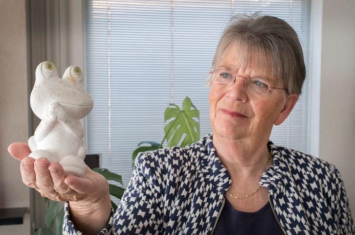 Annie van Leuken met haar gipsen kikker die ze jaren geleden voor Moederdag heeft gekregen van haar zoon.