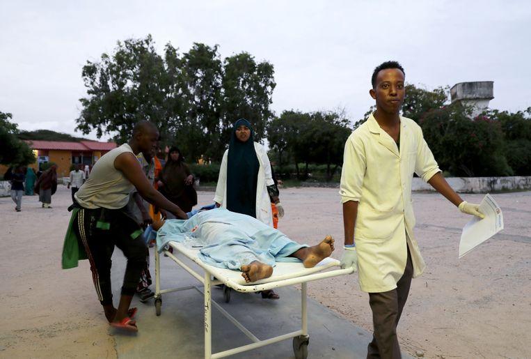 Ambulanciers vervoeren een gewonde hotelgast in Mogadishu. Beeld REUTERS