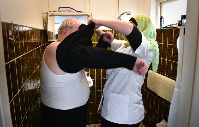 In een kleine doucheruimte is de anderhalvemeterregel voor thuiszorgmedewerkers en cliënten onuitvoerbaar. Beeld Marcel van den Bergh / de Volkskant