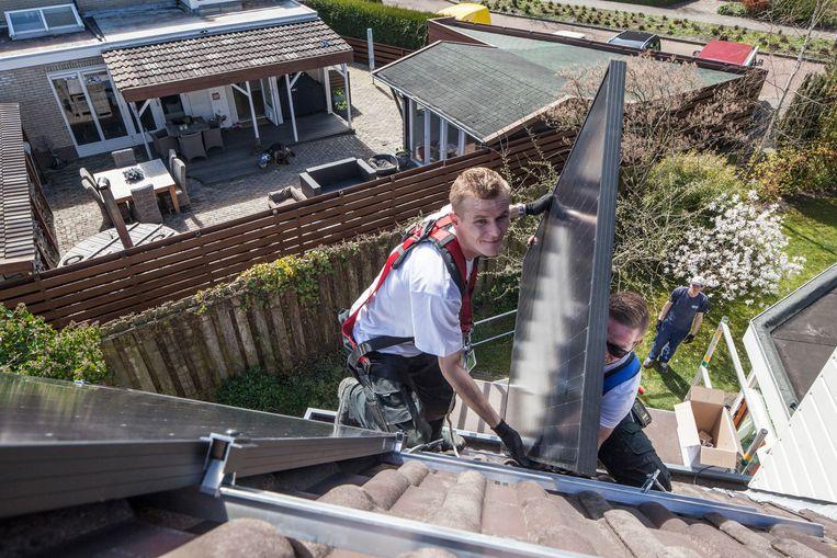 De plaatsing van zonnepanelen op een woning in Zuidwolde, Groningen.  Beeld Harry Cock / de Volkskrant