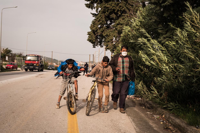 Een vader en zijn twee kinderen in de buurt van het tijdelijke tentenkamp, dat almaar meer een permanent gegeven blijkt te worden. Beeld Nicola Zolin
