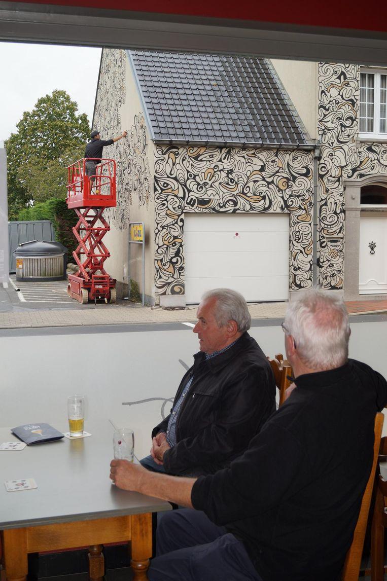Mark en Willy houden de kunstenaar in de gaten terwijl de opnames in café Wilro lopen.