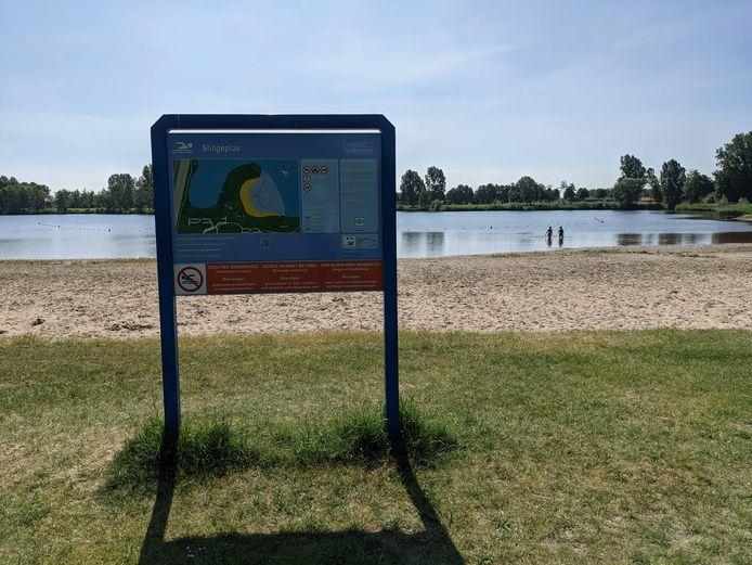 Het algemene informatiebord bij de Slingeplas waarschuwt voor blauwalg. De aanwezige zwemmers nemen het risico voor lief.