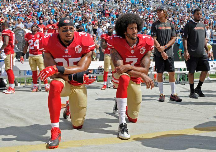 Quarterback Colin Kaepernick (r) knielend tijdens het Amerikaanse volkslied.