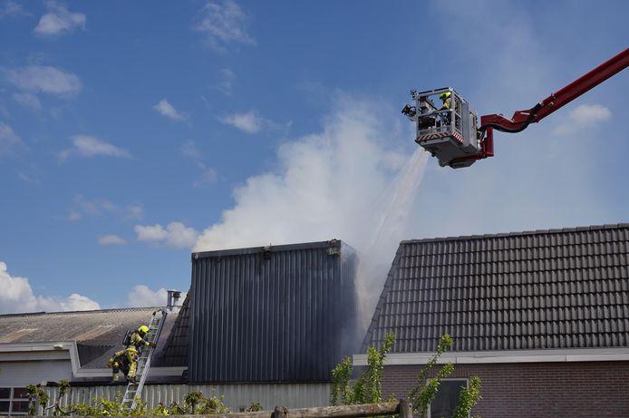 De brandweer bestrijdt het vuur in de opslagbunker aan de Tielsestraat in Herveld met een hoogwerker.