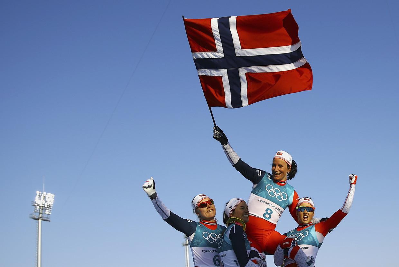 Langlaufer Marit Björgen wordt door haar landgenoten gedragen na het winnen van de 30 kilometer klassieke stijl. Beeld REUTERS
