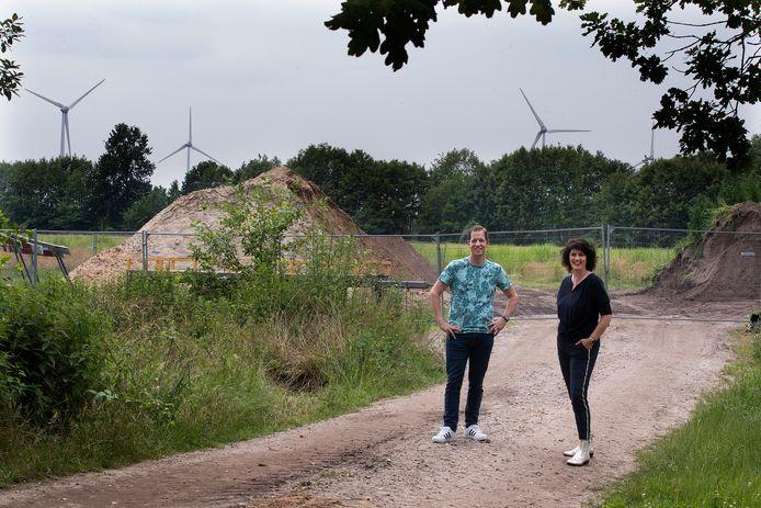 Bart Peters en Ester Reusink aan de rand van hun wijk, op de plek waar nieuwbouw moet komen. Op de achtergrond de bestaande windmolens van Hagenwind.
