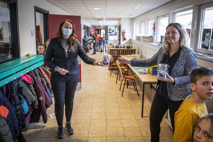 Wethouder Hilde Berning (L) overhandigt de leerkrachten van de Mariaschool in Vasse een blik Kanjers, mini stroopwafels als dank voor de inzet in de afgelopen periode. Ze overhandigt het aan Bernadette Mulder.