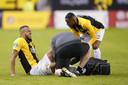 Grot vergaat van de pijn, terwijl Vitesse's fysiotherapeut Jos Kortekaas de voetballer behandelt. Joshua Brenet maakt zich zorgen om de aanvaller.