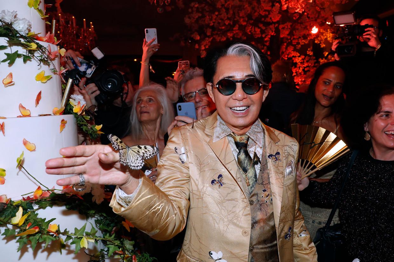 Zijn bedrijfje groeide uit tot een wereldwijd modemerk en droeg niet zijn achternaam, maar zijn voornaam. Ontwerper Kenzo Takada, hier te zien op zijn 80ste verjaardag in 2019, overleed zondag aan covid-19. Beeld Getty Images