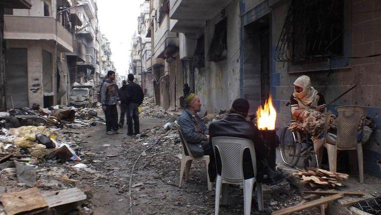Inwoners van Homs houden zich warm rondom een vuur in een van de belegerde wijken van de stad. Beeld reuters