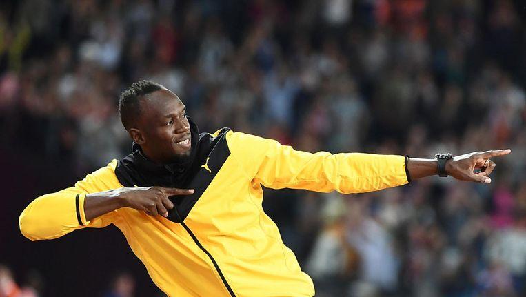 Usain Bolt doet zijn 'bliksemschichtgebaar' tijdens de laatste dag van het WK in Londen. Het gebaar is het logo van de restaurants. Beeld AFP