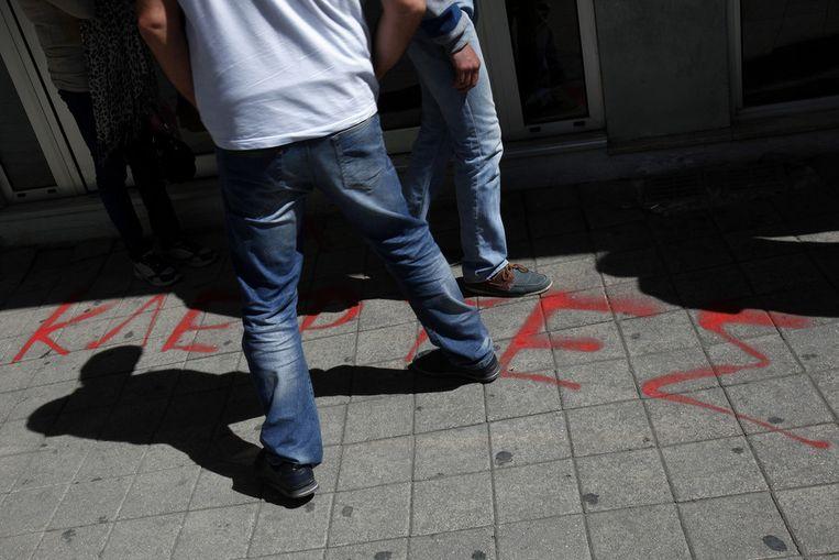 Voor de deur van de Laiki Bank op een centraal plein in Nicosia staat met rode letters 'Dieven' geschreven. Beeld ap