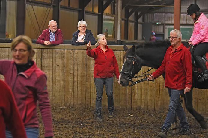 """Bij Manege De Belle in Etten-Leur rijden mensen met een beperking paard onder leiding van Jet van Dam (staand, midden). ,,Het is erg belangrijk voor de ruiters."""""""