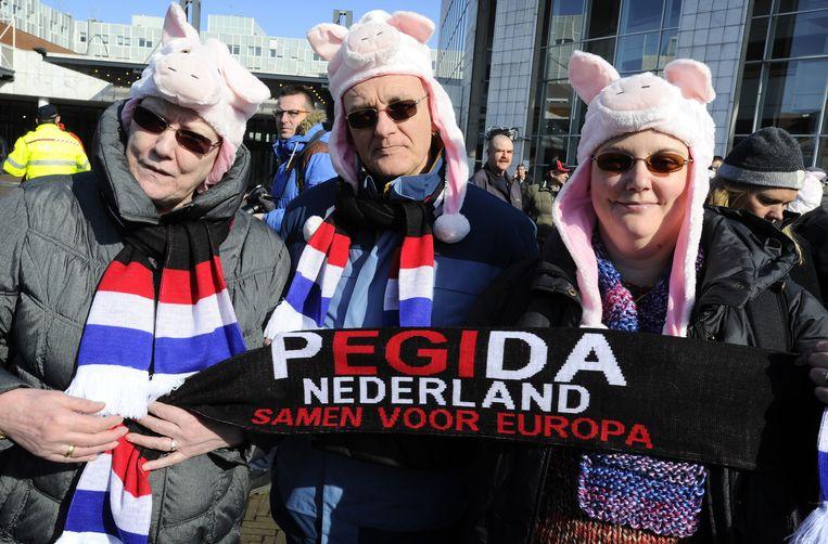 Aanhangers van Pegida kwamen uit solidariteit met voorman Wagensveld met varkenskoppen naar de demonstratie in Amsterdam. Beeld ANP