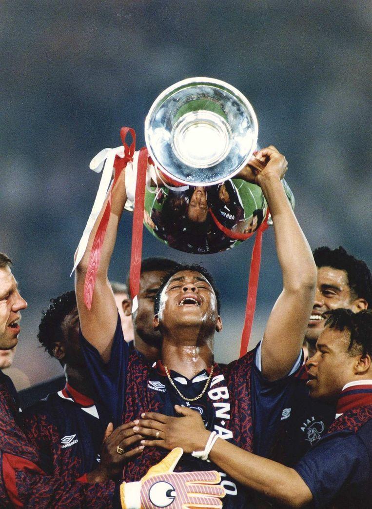Patrick Kluivert, die het enige en winnende doelpunt maakte tegen AC Milan, houdt de beker omhoog. Beeld ANP