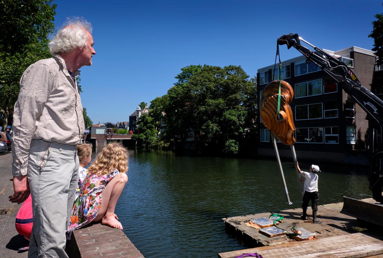 Onder toeziend oog van kunstenaar Gerhard Lentink wordt het oor teruggeplaatst in het water van de Spuihaven.