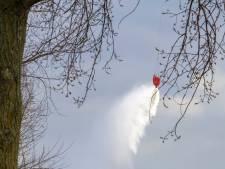 Luchtmachthelikopters oefenen met water scheppen boven Bergsche Maas