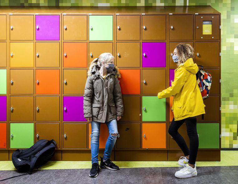 Leerlingen van een middelbare school dragen mondkapjes in de gang.  Beeld ANP