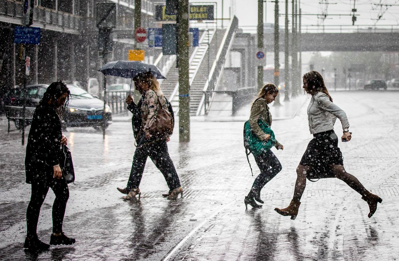 Voorbijgangers lopen door een stevige hoosbui in Den Haag.