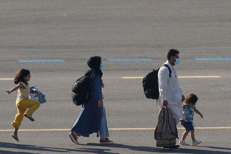 Een familie uit Afghanistan komt aan op de militaire luchthaven van Melsbroek.  Beeld REUTERS