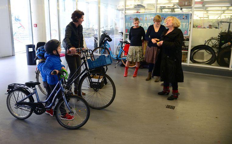 Schepen van Cultuur Denise Vandevoort (rechts) deelt fietslampjes uit aan de kinderen die met de fiets kwamen.