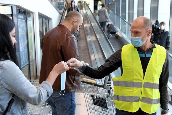 Een supermarktmedewerker overhandigt een klant met handschoenen en een tangetje een mondmasker voor zij de supermarkt binnengaat.