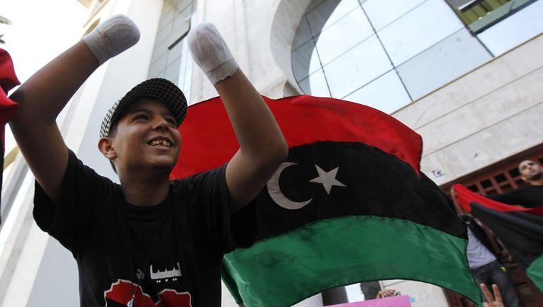 Een gewonde Libische jongen viert feest wanneer hij hoort dat Kaddafi gedood is. © ANP Beeld reuters