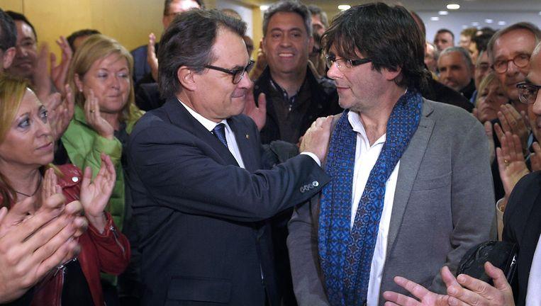 Artur Mas (links) zet een stap opzij en gunt Carles Puigdemont het ambt van Catalaans minister-president. Beeld AFP