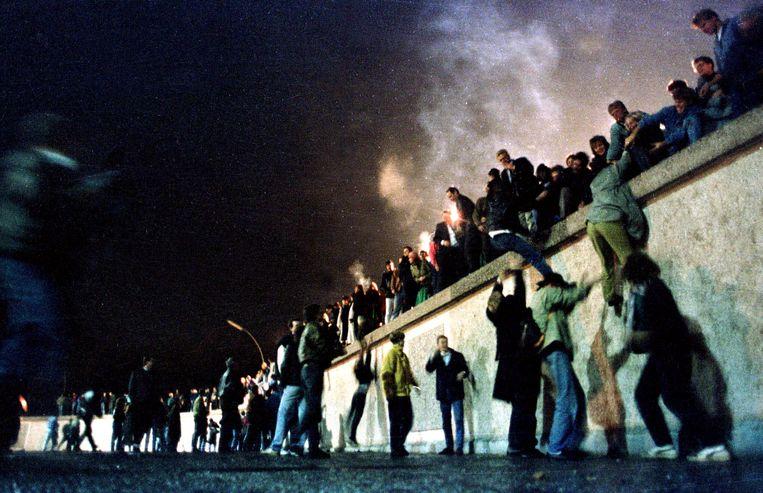 November 1989: mensen klimmen over de Berlijnse Muur nadat bekend raakte dat de grens tussen Oost- en West-Duitsland wordt opgeheven. Beeld REUTERS